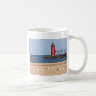 Escena de la playa con las gaviotas y el faro taza