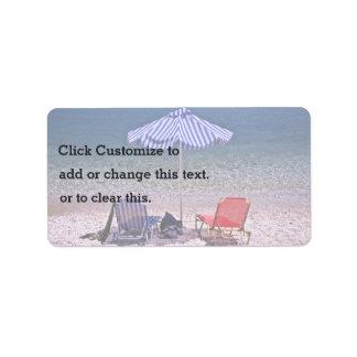 Escena de la playa con las sillas de reclinación etiqueta de dirección