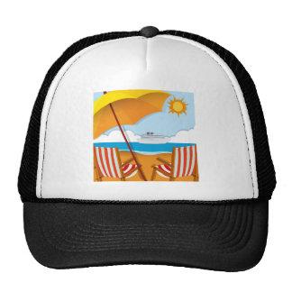 Escena de la playa con las sillas y el paraguas gorras de camionero