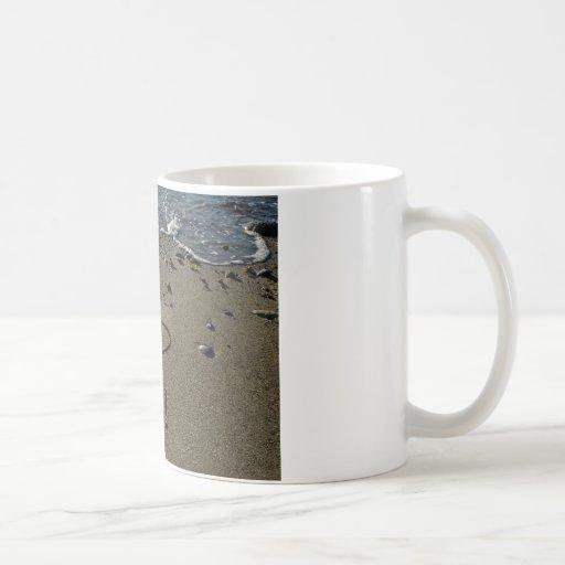 Escritura en la arena tazas de café