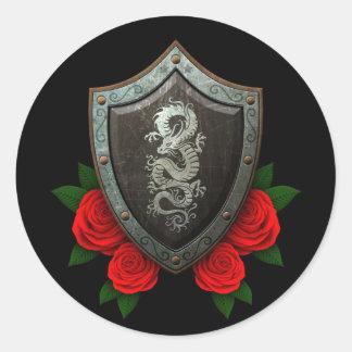 Escudo chino gastado del dragón con los rosas rojo etiquetas redondas
