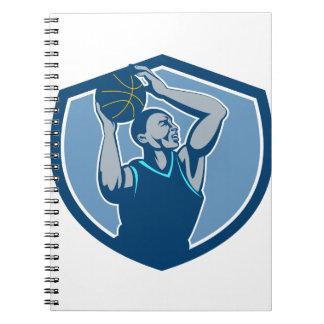 Escudo de la bola del jugador de básquet que libros de apuntes