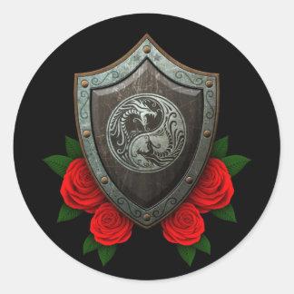 Escudo gastado de los dragones de Yin Yang con los Etiqueta Redonda