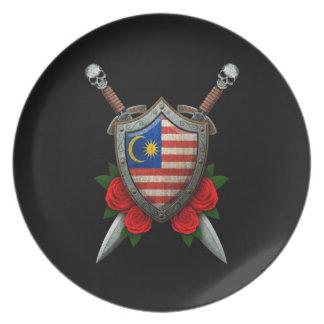 Escudo y espadas malasios gastados de la bandera c platos