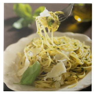 Espaguetis con albahaca y parmesano en la placa, azulejos cerámicos