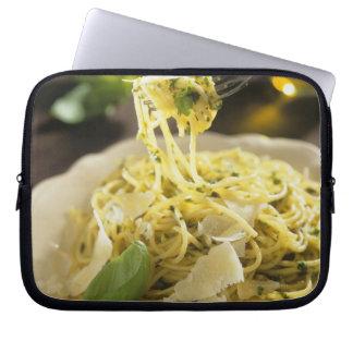 Espaguetis con albahaca y parmesano en la placa, funda ordendadores
