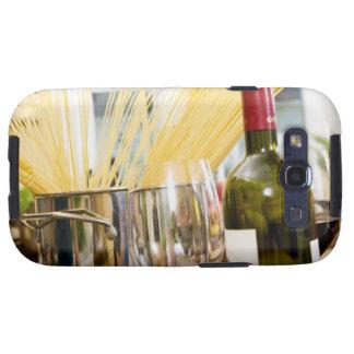 Espaguetis en cacerola con la botella y los vidrio galaxy SIII coberturas