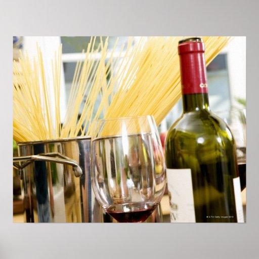 Espaguetis en cacerola con la botella y los vidrio impresiones