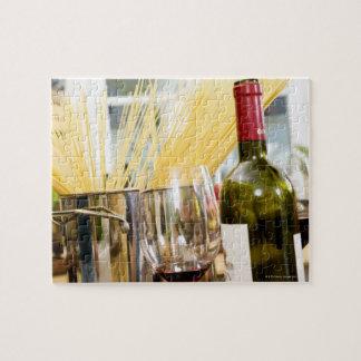 Espaguetis en cacerola con la botella y los vidrio puzzles con fotos