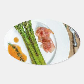 Espárrago verde con el jamón y la salsa pegatina ovalada