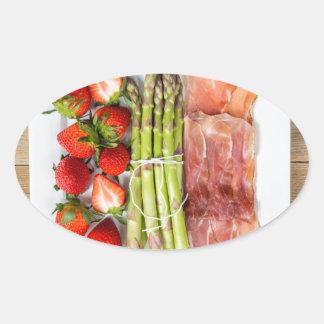 Espárrago verde con el jamón y las fresas pegatina ovalada