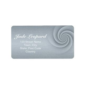 Espiral de plata en textura cepillada del metal etiqueta de dirección