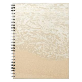 Espuma en colores pastel de la arena y del mar de  libro de apuntes con espiral