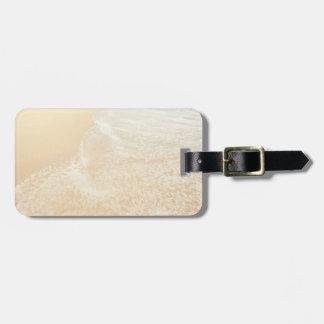 Espuma en colores pastel de la arena y del mar de  etiqueta de maleta