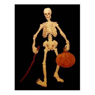 Esqueleto del vintage que sostiene un palillo y postal