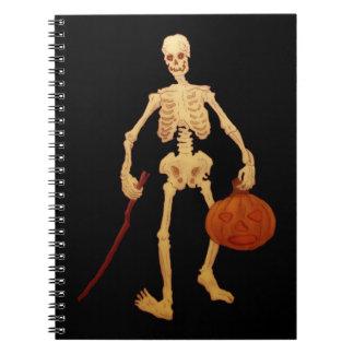 Esqueleto del vintage que sostiene un palillo y un libreta espiral