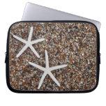 Esqueletos de las estrellas de mar en la playa de  funda portátil
