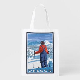 Esquiador que admira el poster del viaje del bolsas de la compra