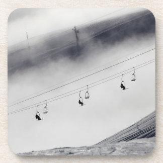 Esquiadores en una elevación de silla posavaso