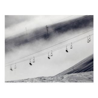Esquiadores en una elevación de silla tarjeta postal