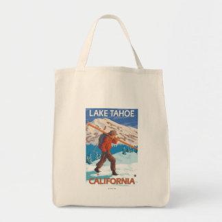 Esquís de la nieve del esquiador que llevan - el bolsa de mano