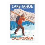 Esquís de la nieve del esquiador que llevan - el l postal
