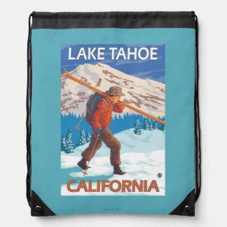 Esquís de la nieve del esquiador que llevan - el mochilas