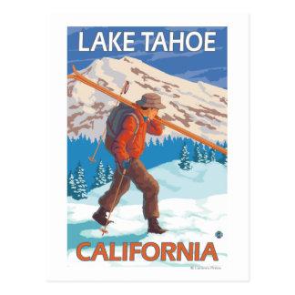 Esquís de la nieve del esquiador que llevan - el postal