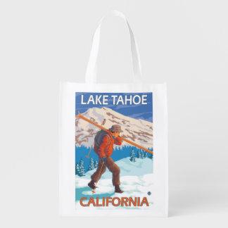 Esquís de la nieve del esquiador que llevan - el bolsas para la compra