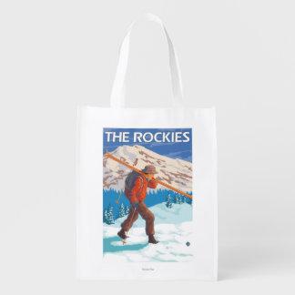 Esquís de la nieve del esquiador que llevan - los bolsa de la compra