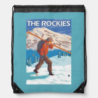 Esquís de la nieve del esquiador que llevan - los mochilas