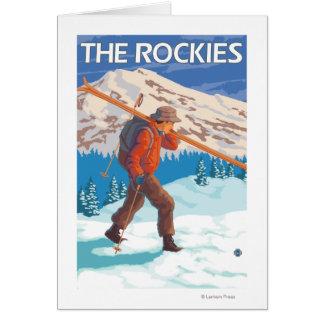 Esquís de la nieve del esquiador que llevan - los  tarjeta