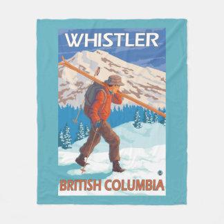 Esquís de la nieve del esquiador que llevan - manta de forro polar