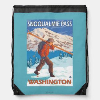 Esquís de la nieve del esquiador que llevan - paso mochila