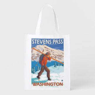 Esquís de la nieve del esquiador que llevan - paso bolsas reutilizables