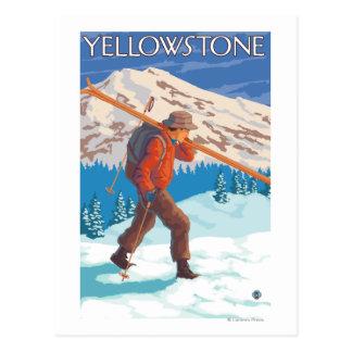 Esquís de la nieve del esquiador que llevan - postales