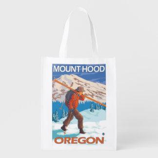 Esquís de la nieve del esquiador que llevan - bolsa de la compra