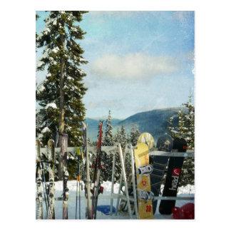 Esquís y snowboard en el top de la montaña postal