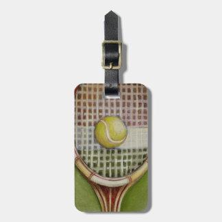 Estafa de tenis con la bola que pone en corte etiquetas para maletas