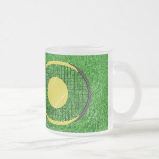 Estafa y bola de tenis en césped taza de café esmerilada