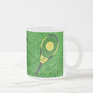 Estafas y bolas de tenis en césped taza de café esmerilada