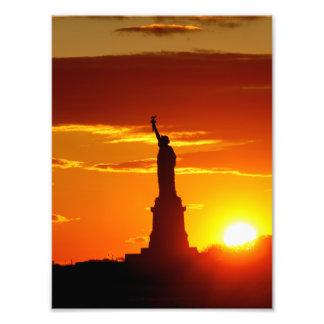 Estatua de la libertad en la puesta del sol fotografías