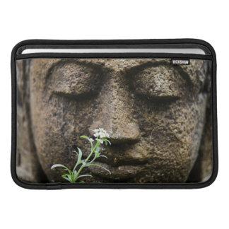 Estatua de piedra del jardín con la flor funda macbook air