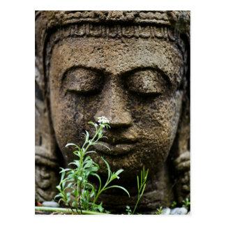 Estatua de piedra del jardín con la flor postal