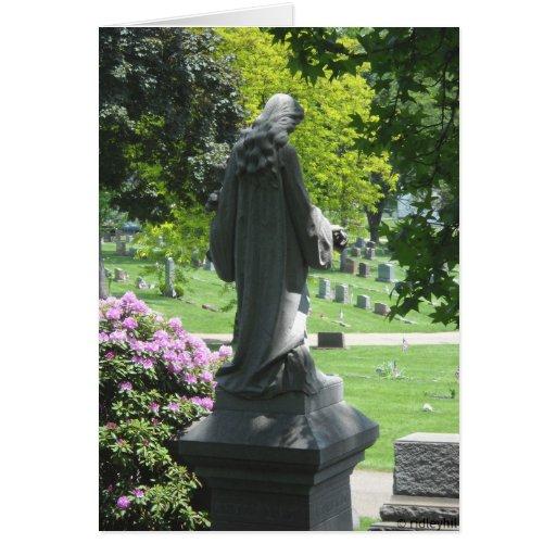 Estatua del cementerio con las hojas y las flores tarjeton