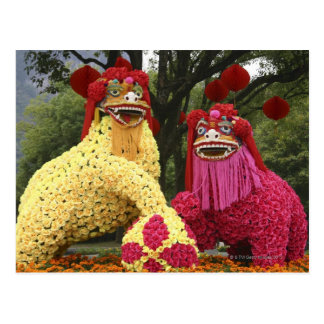 Estatuas de dos dragones cubiertos con las flores postales