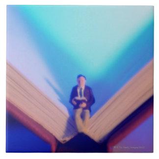 Estatuilla que se sienta en el libro abierto azulejo cuadrado grande