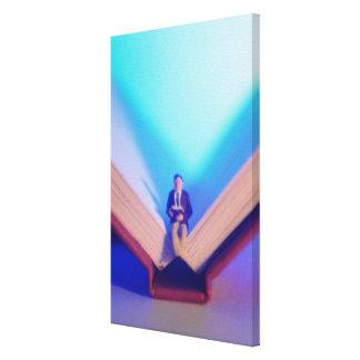 Estatuilla que se sienta en el libro abierto impresion en lona