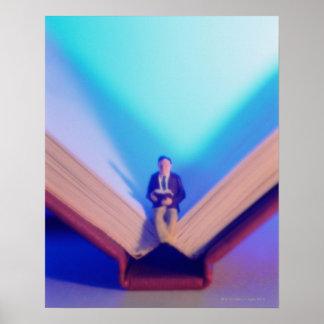 Estatuilla que se sienta en el libro abierto póster