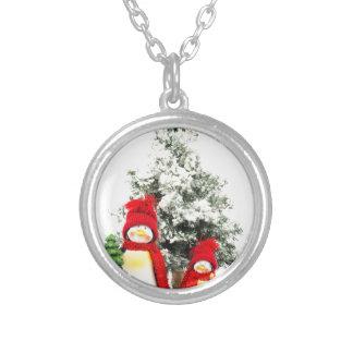 estatuillas del pingüino con el árbol de navidad collar plateado